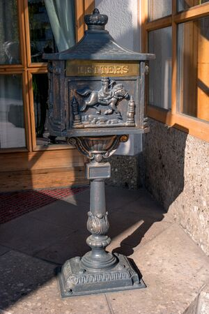 Old black metal mailbox on a metal base. The bas-relief is made on the box - the postman on a horse is blowing a horn. The mailbox and the base are richly decorated Banco de Imagens