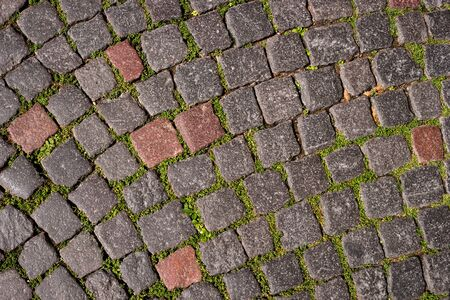 Abstract background of old cobblestone pavement. Close-up.