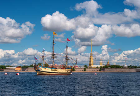 Marine parade in St. Petersburg. Sailing Russian frigate Poltava on the Neva in the center of St. Petersburg. Panaroma of the Peter and Paul Fortress.