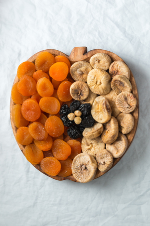 Dried fruits apricots figs prunes hazelnuts on a white background in the shape of an apple with space for text or title