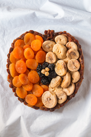 Dried fruits apricots figs prunes raisins hazelnuts on a white crumpled texture in the shape