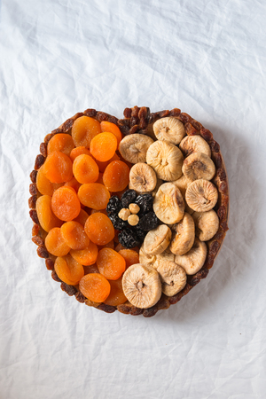 Dried fruits apricots figs prunes raisins hazelnuts on a white texture background in the shape of an apple with space for text or title