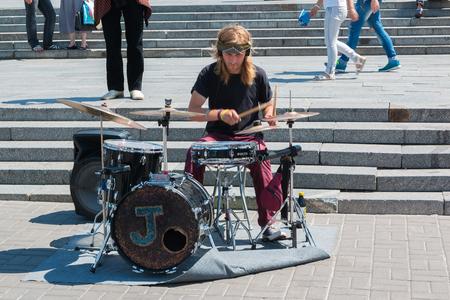 Kyiv, Ukraine - 07 08 2017: The street musician plays on drums Editorial