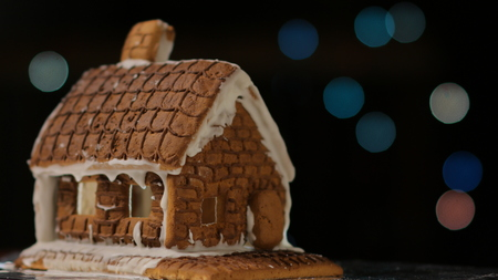 Gingerbread house with blue lights bokeh circles blur Christmas garland Happy New Year Banco de Imagens
