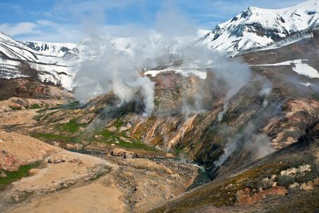 and plot: Mountainous terrain and  gas emissions in the Valley of Geysers in Kamchatka. The plot of the volcanic and thermal activities in the Kronotsky nature reserve. Russia. Stock Photo
