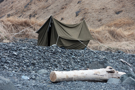 far: Canvas tent on the rocky shore. A small tent after the wind on the shore of the sea of Okhotsk, far East, Russia.