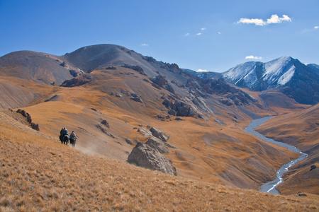 Three hunters on horses in mountains Tien-Shan. The Issyk-Kul region, Kyrgyzstan,