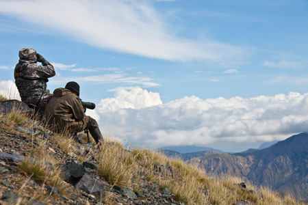 inaccessible: Hunting ibex in the Tien Shan mountains determine trophy quality animals through binoculars and a telescope, Kyrgyzstan. Steep slopes, cliffs, rock slides in inaccessible mountains.