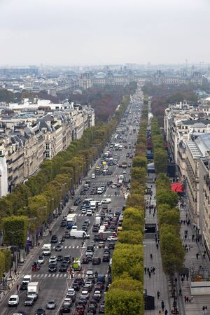 Champs Elysees - the main street of Paris. View of the city center and the Louvre from the Arc de Triomphe in autumn. Roadway, transportation, and homes along the Champs Elysees in October.