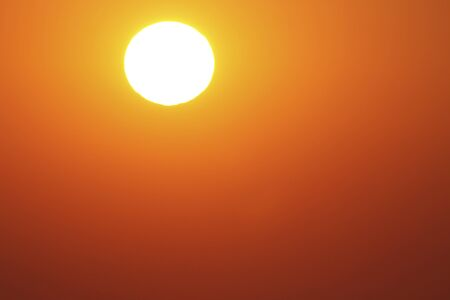 Orange sky around the white of the sun. Bright dazzling white sun in a clear red sky with shades 스톡 콘텐츠