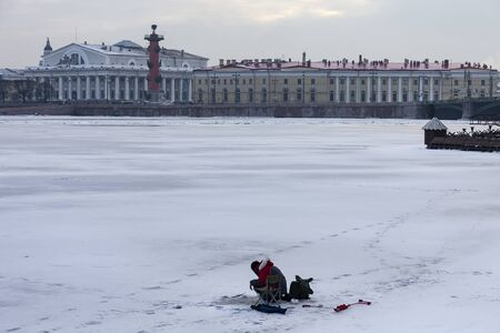 Ice fishing on the Neva river ice in the center of St. Petersburg. A fisherman catches fish in the historical center of the Northern capital of Russia against the background of the Spit of Vasilievsky island and Rostral columns