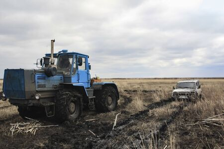 A tractor pulls a stuck car out of the fields . A wheeled tractor is towing a light off- road vehicle from a difficult arable land . Spring goose hunting.