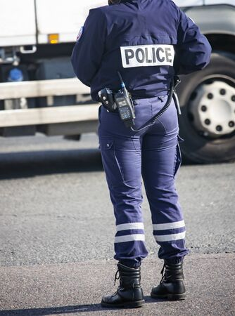 Policeman on a street in Paris controls public order. A fully equipped woman policeman monitors traffic management. Equipment, walkie-talkie, handcuffs, weapons of the servant of the law.