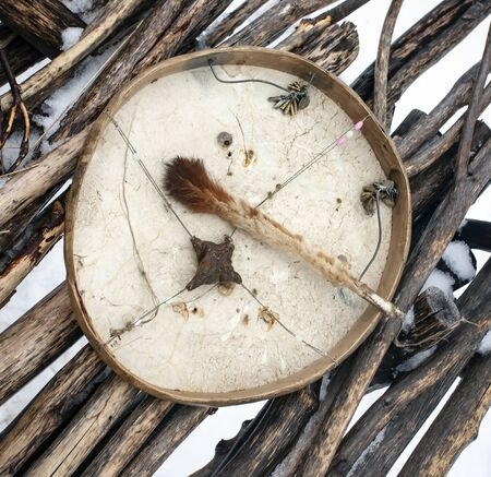 Shaman tambourine with a clapper on the background of yaranga flooring. The ritual instrument of the Koryak shaman is a tambourine made of leather, wood and animal tendons with metal rattles.