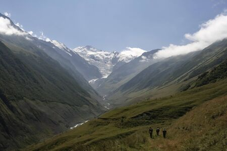 Hunters climb the mountains through the gorge. Three men with weapons and staffs go up the slope of the Carmadon gorge. Caucasus, Ossetia-Alania.