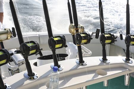 Spinning rods with reels installed in holders before fishing on a boat. Equipment for sea trophy fishing on a fishing yacht.