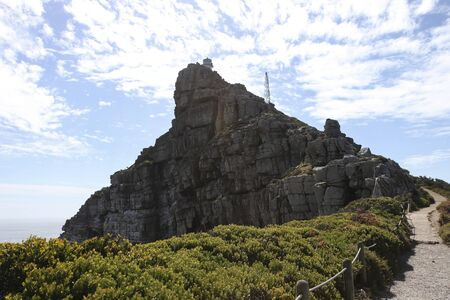 The upper tower of the lighthouse on the rock of the Cape of Good Hope. A lighthouse at the highest point of the cliff on the southern tip of the Cape Peninsula.