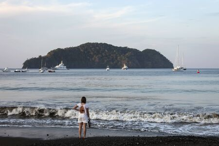 The sunrise and quiet surf on the coast of the Pacific ocean. A girl in the morning on the beach looks at the Bay with yachts and a tropical island.
