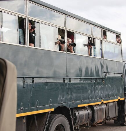 Photographing animals from a camper during a Safari. Tourists take pictures of nature and animals from the Windows of the car in a national Park in Africa.