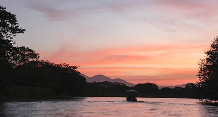 Pink sky at sunset on the Rio Frio river in Costa Rica. Boat on the river in the evening in the rays of the setting sun in Central America. 스톡 콘텐츠 - 148261468