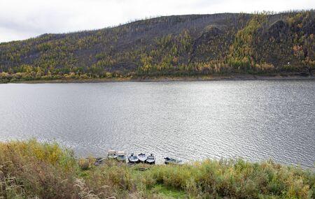 Podkamennaya Tunguska river and motor boats near the shore in autumn. Siberian taiga and the banks of the Tunguska river near the village of Tura. 스톡 콘텐츠