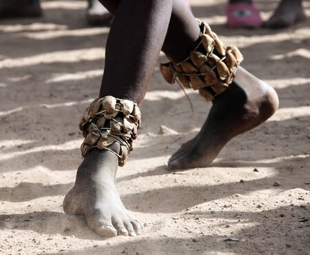 Feet of a black teenager dancing on the sand folk ritual dance. The right naked leg of a black African with an ankle ornament in the sand and dust.
