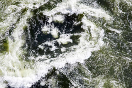 The surface texture of a stream of clear river water when viewed from above. Jets, foam, spray, currents and circulation of the water mass of the Zambezi river after Victoria falls when viewed from the bridge. 스톡 콘텐츠 - 150647350