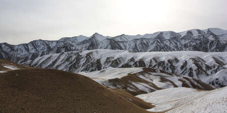 Panorama of a mountain pass in the evening sun in winter. Landscape of a mountain pass with rocks, stones, snow and animal tracks.