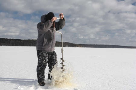 A fisherman pulls an ice drill out of the ice on a reservoir in winter. A man drills a hole in the ice cover on the lake.