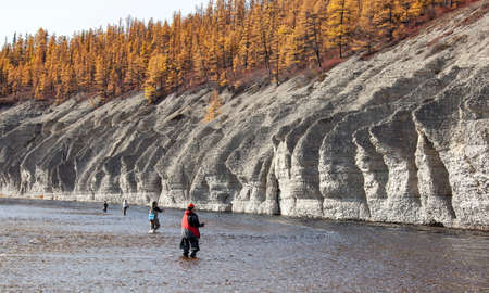 Fishermen catch fish with spinning rods on the Siberian river. Four men with fishing rods stand in a mountain river in autumn. Sport fishing in Siberia.
