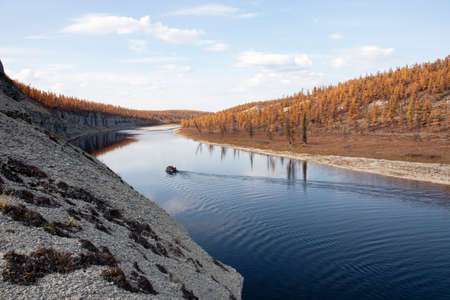 Landscape with a boat on the surface of the river at sunset in autumn. Siberian river in the evening in September. Krasnoyarsk territory, Siberia, Russia, Asia,