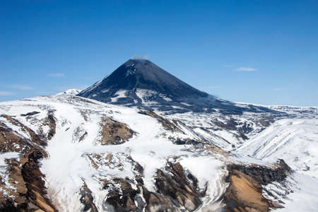 View of the correct cone of the Karymsky volcano in the spring after a snowfall. Geothermal activity on the slopes of the volcano in may from a helicopter.