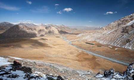 View of the landscape with a valley and riverbed in the mountains. Mountain terrain on the border of Kyrgyzstan and China. Asia, 스톡 콘텐츠