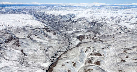 Panorama of snow-capped mountains from a helicopter. The landscape created by volcanic activity on the Kamchatka Peninsula. 스톡 콘텐츠 - 153404699