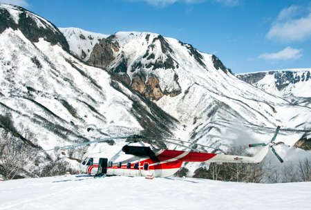 The helicopter is sitting in the snow in a mountainous area. Rotorcraft on a wild helicopter pad in the snowy mountains of Kamchatka. 스톡 콘텐츠 - 153404701