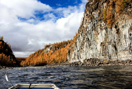 The rise of a Siberian river in a rocky gorge in the fall. Oncoming water flow in the mountain taiga in the North of the Krasnoyarsk territory. 스톡 콘텐츠 - 153404705