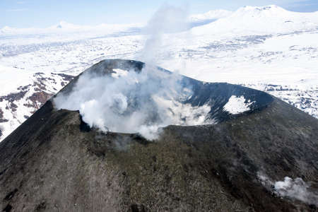The mouth of an active volcano, with smoke and steam, when flying it by helicopter. The top and crater of the Karymskaya Sopka volcano in Kamchatka in early may. 스톡 콘텐츠 - 153404706
