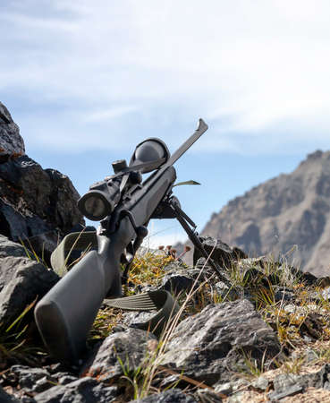 Hunting rifle with optical sight on bipods prepared for hunting in the mountains. Sniper weapons in the mountains before shooting.