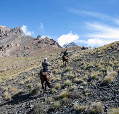 Riders on horses with weapons climb the mountain slope. Three hunters on horseback are moving towards the pass. 스톡 콘텐츠 - 153386132