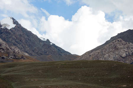 View of Cumulus clouds over the pass in the high mountains. A complex mountain pass with steep slopes, rocks and precipices is covered with clouds. Asia,