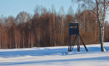 A tower for hunting wild animals on the edge of a snow-covered field in winter. Hunting tower on the edge of the forest on a frosty day in January.