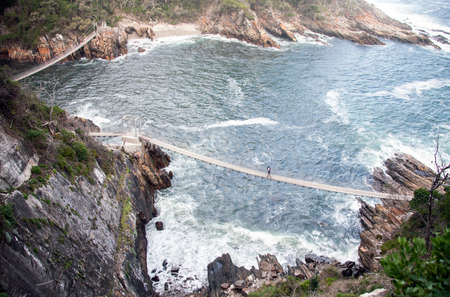 Suspended pedestrian bridges over the cliffs and bays in the Park Tsitsikama. Silhouettes of tourists on the route over rope bridges over the coastline in the rainforest zone of the national Park in South Africa.