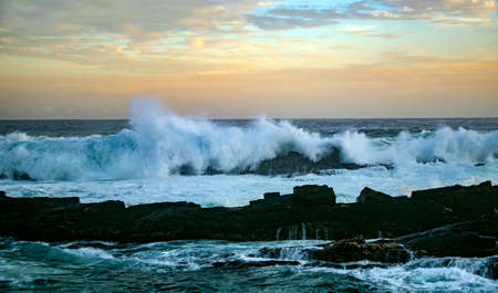 Sunset and storm waves on the ocean coast. Evening sea surf on the rocky coast of Tsitsikama national Park in South Africa. 스톡 콘텐츠 - 155170705