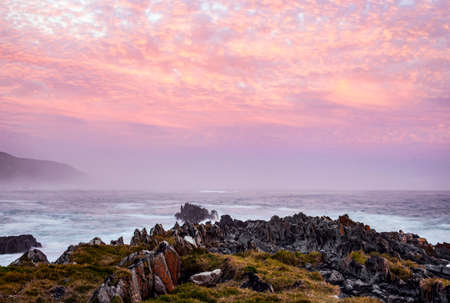 Sunset over the rocky coast of the ocean in a storm. Evening sky with pink clouds over the sea coast during a strong wind. Africa 스톡 콘텐츠