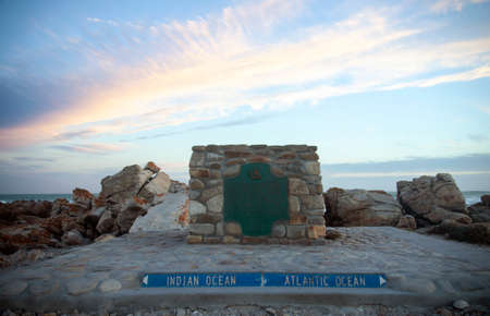 Sunset over Cape Agulhas marks the confluence of two oceans. The confluence of the Atlantic and Indian oceans with a memorial sign in the very South of Africa. 스톡 콘텐츠 - 155170707