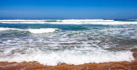 Ocean surf on a sandy beach on a Sunny day. Foam, spray and waves of sea water at the edge of the ocean shore. 스톡 콘텐츠 - 155170715