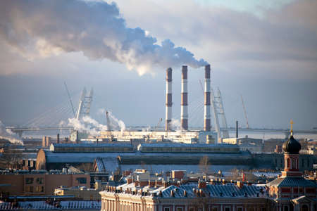 Smoke from the pipes of a thermal power plant in the frosty air over St. Petersburg. Air pollution of St. Petersburg by gas emissions and smoke in the cold season. 스톡 콘텐츠 - 155222528