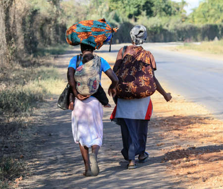 Two African women with a child and a load walk along the road. Black women in traditional colored clothing with a child and things on their shoulders and on their heads are walking.