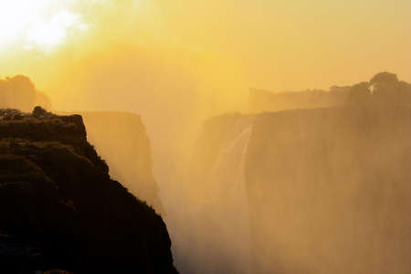 Sunrise over the mist and water dust of Victoria Falls in shades of red, orange and yellow. The rays of the morning sun illuminate the water dust over the waterfall on the Zambezi River.