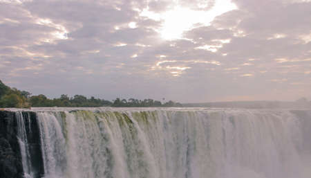 View of a cloudy landscape with morning sun rays over Victoria Falls. The rising sun breaking through the clouds over the water flows of the Zambezi River. Africa,